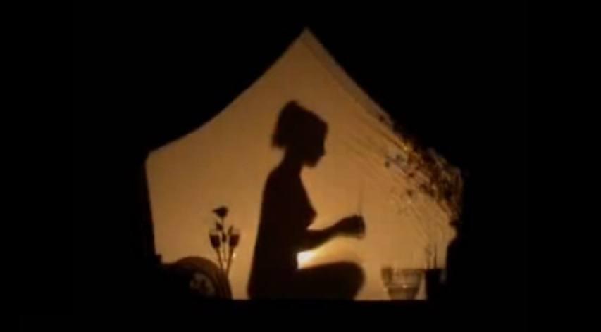 Tantra masáž, hra světla - silueta nahé ženy před svíčkou